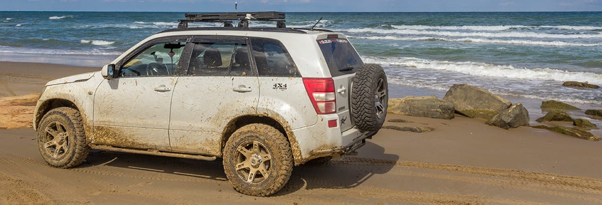 White Car having Muddy Tires on Beach with Electronic Rust Protection